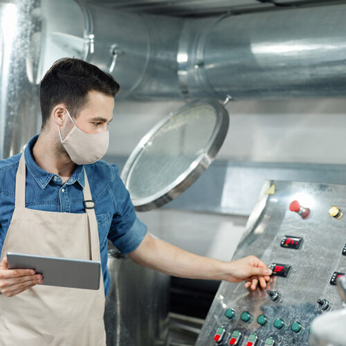 Management of large brewery during social distancing. Young attractive male worker in apron and protective mask presses button on equipment and holds tablet in interior of plant, free space